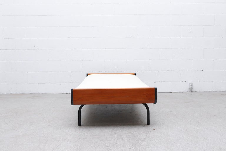 Beautiful midcentury Friso Kramer style daybed with lightly refinished teak ends and grey enameled square metal legs for Auping. Freshly upholstered off-white fabric on wire mesh support with original manufacturer stamp. In original condition with