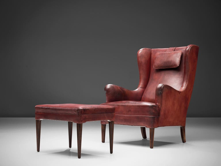 Frits Heningsen, lounge chair with ottoman, leather, Denmark, 1940s   Danish wingback lounge chair by Frits Heningsen (1889-1965) in the 1940s. Both the chair and the ottoman are fully restored and feature their original leather that shows admirable