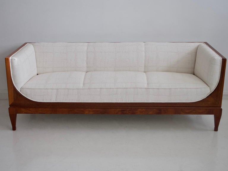 Beautiful box-shaped mahogany sofa designed by Frits Henningsen and produced in the 1940s. Front with rounded sleigh-shaped sides, tapered legs. Reupholstered in white textured fabric.