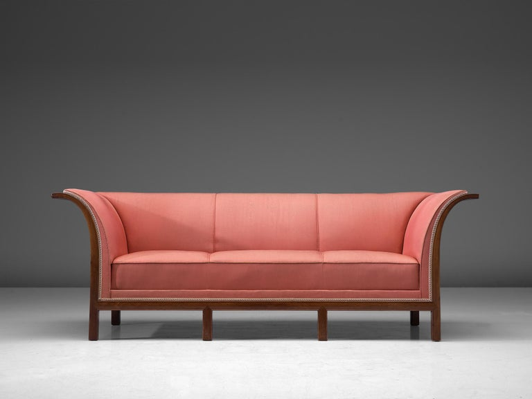 Frits Henningsen, sofa in mahogany and pink fabric, Denmark, 1930s.  This classic sofa was designed and produced by master cabinet maker Frits Henningsen around the 1930s. The basic design is well balanced, showing an interesting contrast between
