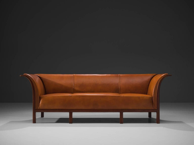 Frits Henningsen, sofa in teak and cognac leather, Denmark, 1930s.  This classic sofa was designed and produced by master cabinet maker Frits Henningsen, circa 1930s. The basic design is well balanced, showing an interesting contrast between the