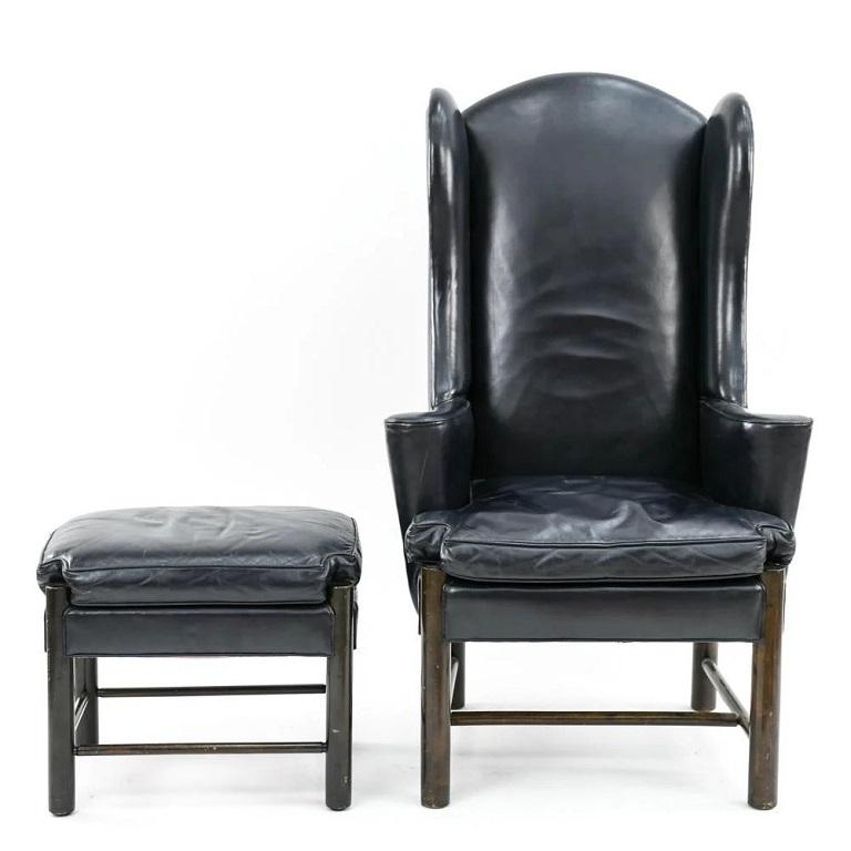 Frits Henningsen style leather wingback chair and ottoman. The chair and ottoman is dark blue leather with a wood frame.