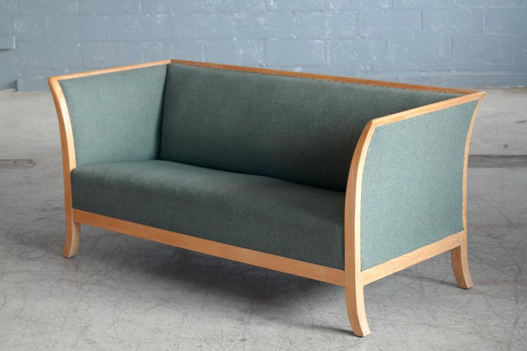 Beautiful and very elegant Frits Henningsen style sofa manufactured and marked with label by Søren Willadsen, Denmark probably sometime in the 1930s-1940s. Framed in oak with the frame extending into flared legs. Later upholstered in sides, seat and