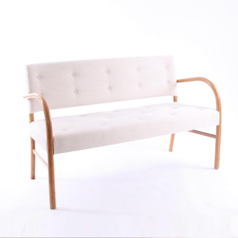 FRITS SCHLEGEL & FRITZ HANSEN - SCANDINAVIAN MODERN  A beautiful and rare sofa bench by Frits Schlegel and manufactured by Fritz Hansen, 1940, with maker's brass plaque and paper label.  The sofa bench is with moulded beech frame and seat and back