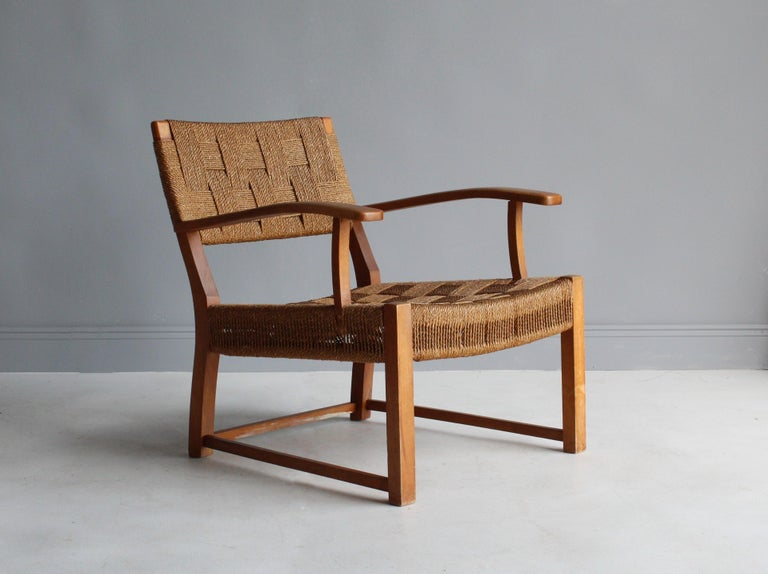 A modernist lounge chair or armchair attributed to Danish architect and designer Frits Schlegel. Frame made of stained birch, bears original seagrass cord.  Other Nordic designers of the period include Kaare Klint, Edvard Kindt-Larsen, Vilhelm