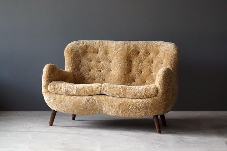 An example of early Danish modernism.  Upholstered in beige sheepskin contrasting dark wooden legs.  Frits Schlegel was a Danish modernist architect active during the same era as Flemming and Mogens Lassen, Philip Arctander, Viggo Boesen.