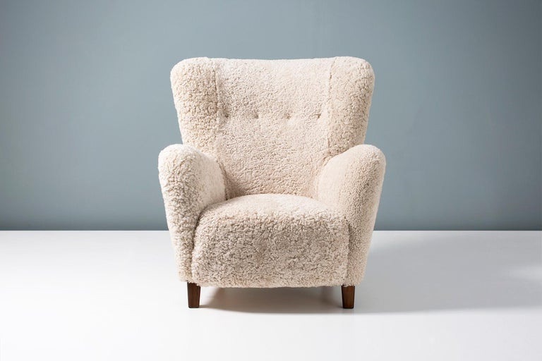 Lounge chair produced by Fritz Hansen in Denmark, between 1940-1960. This model is a variant of the iconic 1669 armchair and has a slightly higher back. The legs are stained beechwood and the chair has been completely reconditioned in our London