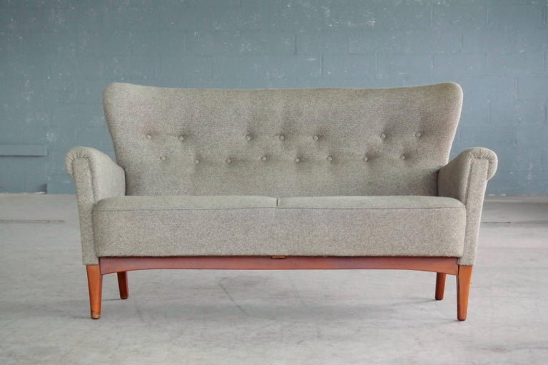 Very elegant settee or two-seat sofa made by Fritz Hansen sometime in the early to mid-1950s in Copenhagen, Denmark. The frame is construed similar to Fritz Hansen's armchairs of the 1940s allowing it to be disassembled without use of tools.