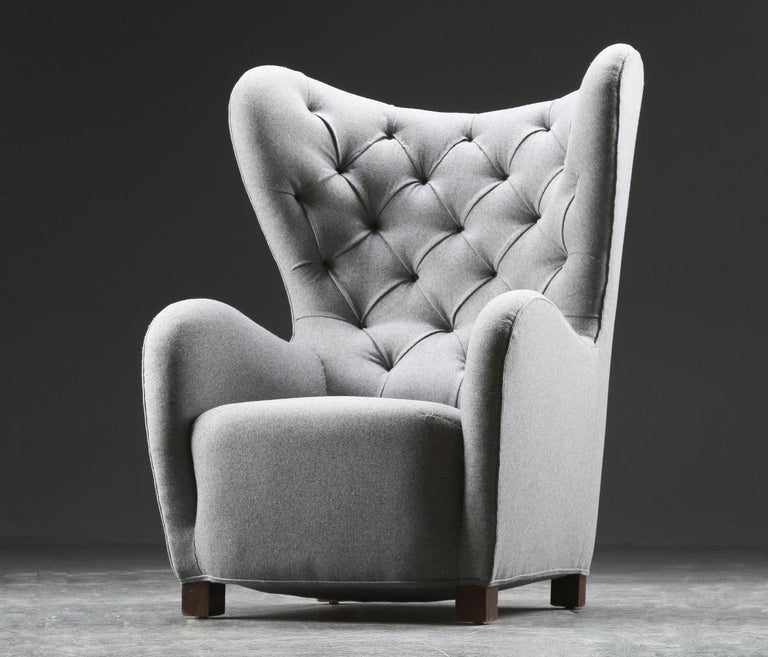 An organic high back / lounge / wingback chair designed and produced by Fritz Hansen in the 1940s. Model number 1672. Newly reupholstered in wool fabric. Buttons in contrasting dark green color.  Litterature: Fritz Hansen Catalogue 1942, page
