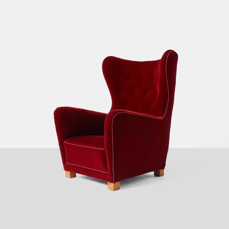 Fritz Hansen lounge chair model #1672 A large scale lounge chair by Fritz Hansen upholstered in a luxurious red velvet with corded trim on block style oak legs. Denmark, circa 1930s.