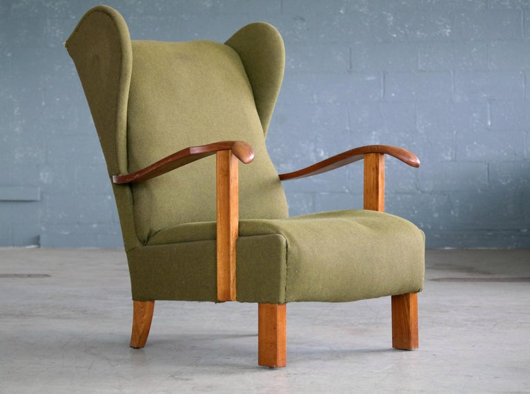 Very cool low swung wing back lounge chair made by Fritz Hansen in Copenhagen, Denmark. The wooden armrests and legs are made of varnished beech wood showing great grain and patina and just minor natural wear. The chair still has the handwritten ink
