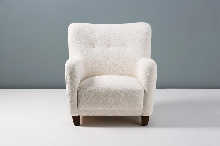 1940s vintage armchair in the manner of Fritz Hansen, produced in Denmark by FDB Mobler. The legs are stained beechwood and the chair has been reupholstered in luxurious bouclé fabric composed of cotton and wool.  Pair available by request.
