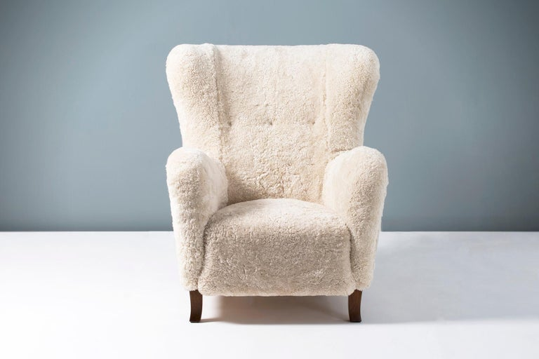 Pair of 1940s vintage wing chairs in the manner of Fritz Hansen, produced in Copenhagen by Christian Sorensen & Co. The legs are stained beechwood and the chair has been reupholstered in luxurious Australian shearling.   Measures: H 98cm, D 80cm,