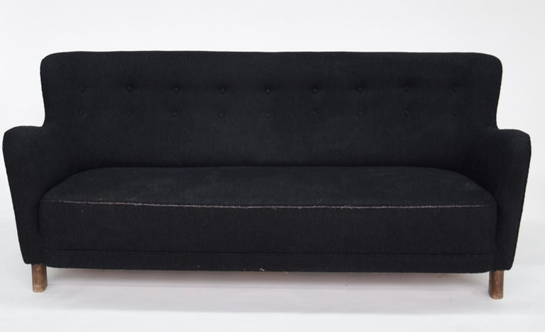 Fritz Hansen three-seat sofa, model 1669A with oval beech legs, upholstered in wool, buttoned back.