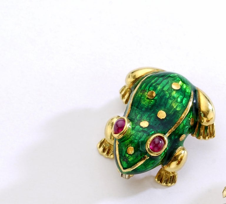 Frog yellow gold green enamel with ruby cabochon eyes Clip Brooch. Chic and Elegant the perfect accessory on a jacket.  Total Length: 1.79 inch (2.00 centimeters). Width at maximum: 1.71 inch (1.80 centimeters).