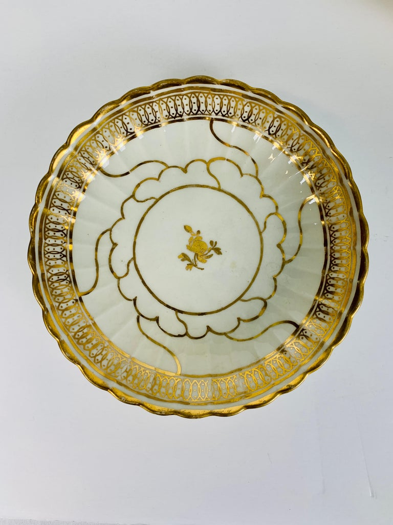 Provenance: The Private Collection of Mario Buatta A group of five elegant Worcester white and gold saucers made in the Regency style in England circa 1810. The white porcelain makes the lustrous Regency period gold stand out. Each piece has