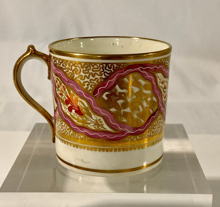 Provenance: The Collection of Mario Buatta We purchased this porcelain cup and saucer from the estate of Mario Buatta.  Made by Miles Mason in England circa 1805 the coffee cup and saucer have an exquisite pink ribbon design with small brick red