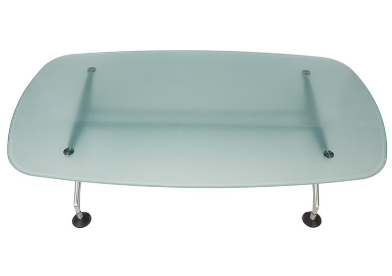 This modern coffee table designed by Antonio Citterio for Vitra, Germany features a slightly curved rectangle made of tempered frosted and slightly colored glass resting on a brushed metal support with four angled legs ending in circular pad feet.