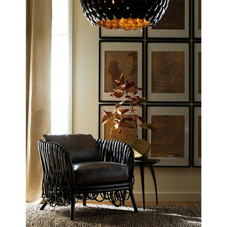 Frou Frou is a contemporary armchair constructed with a hand bent cane frame covered with intricate woven rattan loops in a deep black finish. The seat is upholstered with a premium leather cushion in a graphite tone.   Dimensions: H: 30