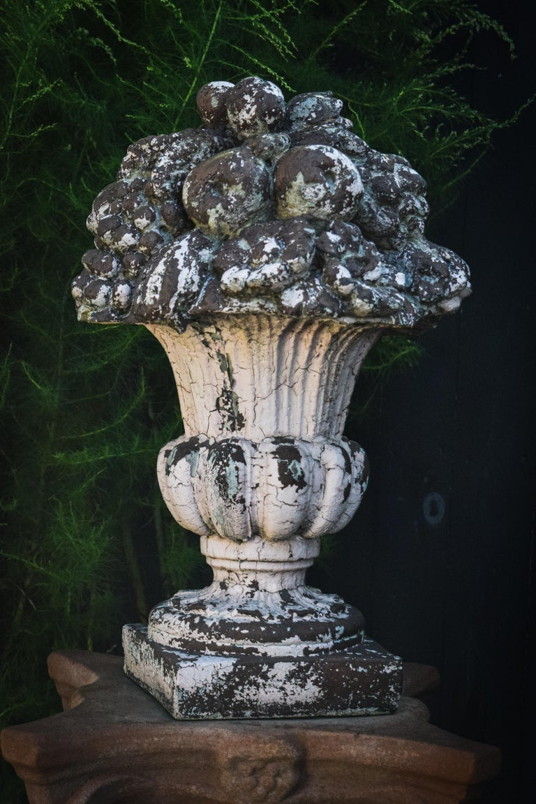 Brimming with fruit out of a traditional urn style base, this sculpture evokes a sense of long-standing abundancy. Weathering consistent with age, each ornament is attractively patinaed with a one of a kind craquelure, allowing the composite stone