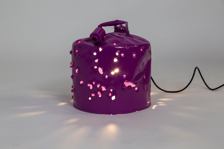 This antique metal gas can was shot with bullets, powder coated and wired as a lamp to become a bold work of art made Charles Linder. He has been making artwork out of bullet-riddled objects for over 30 years. The light coming through the holes has
