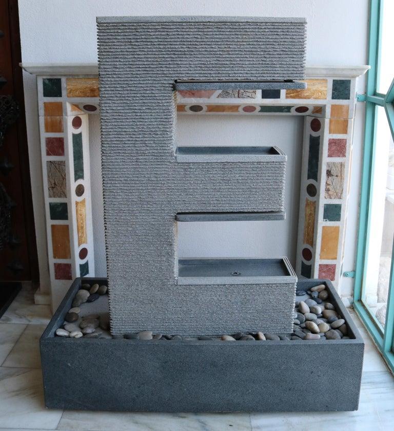 Fuente Moderna realizada en granito negro con base rectangular.