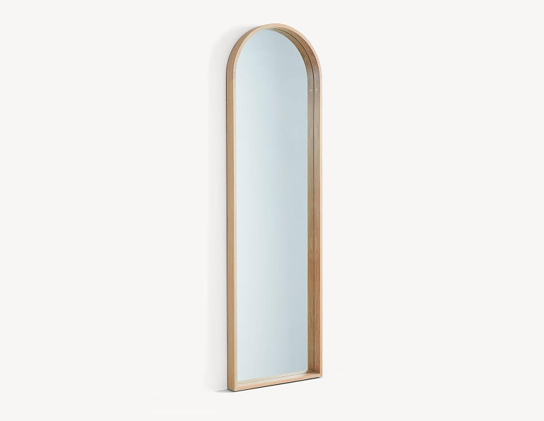 The contemporary Euclid mirror pays homage to the arched doorways that featured in Shaker architecture. The steam-bent arch is connected with brass pinned lap joints and the base of the frame features half-blind dovetails. The mirror floats off the