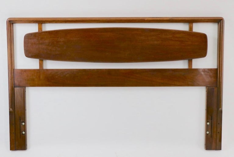 Stylish mid century architectural headboard, from the Rhythm collection, by Lane Furniture. The headboard features an elongated oval, surrounded by a solid walnut rail. Will accommodate a standard full size mattress. Measures: Total W 59.5 x
