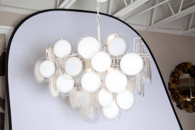 A fully restored, nicely scaled 1970s Vistosi chandelier with clear handblown Murano glass discs with white centres, hung on a newly re-wired, fresh white metal frame. Additional 18 inches of chain and canopy.