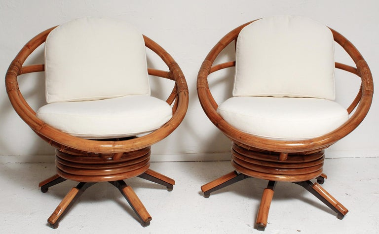 Swing out in this pair of fully restored bamboo swivel chairs with all new foam cushions and cotton twill upholstery.