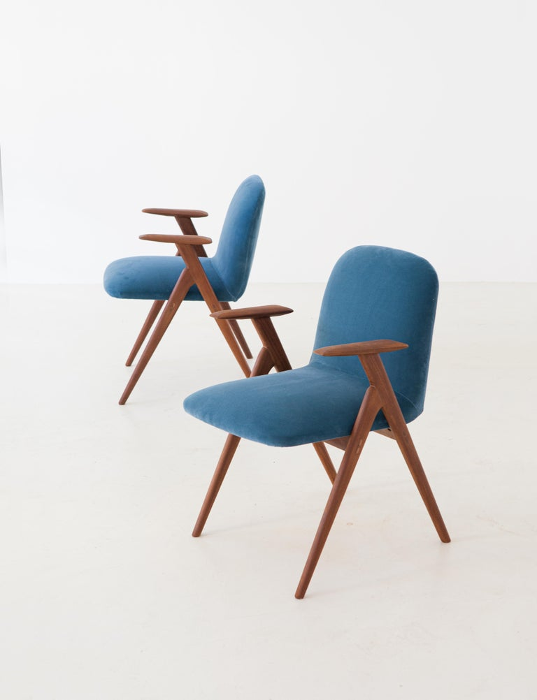 Italian Mid-Century Modern easy chairs in solid teak and light blue velvet upholstery.  Very light and smooth lines for this particular chair  Completely restored: the wooden frame has been polished and finished with little shellac, the cover is