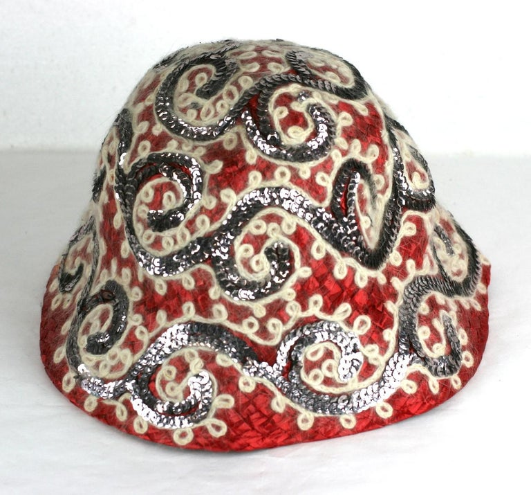 Interesting and striking red straw hat from the 1950's embroidered with swirly purpley sequins and white fuzzy angora yarn. Likely Italian in manufacture and very Prada in its contrasting vibes.  Sally Victor imports for B. Altman. 1950's