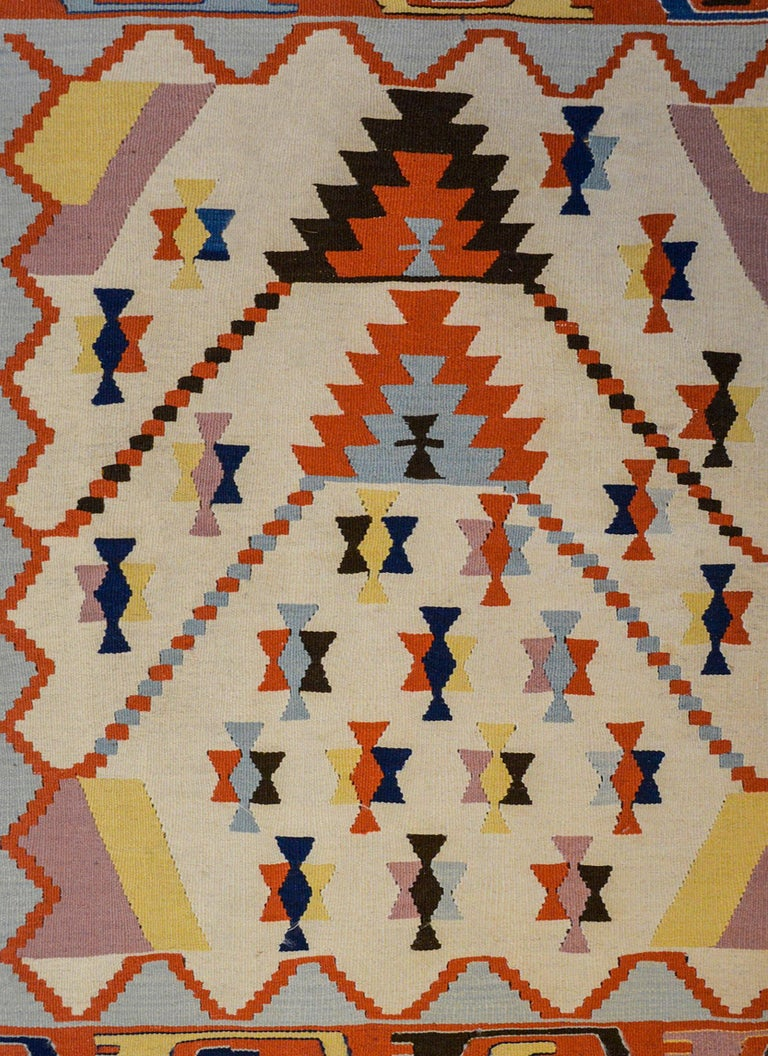 A fun vintage Indian Dhurrie Kilim rug with a bold geometric pattern woven in light and dark indigo, crimson gold, black and white wool surrounded by a pale indigo and crimson zigzag patterned border.