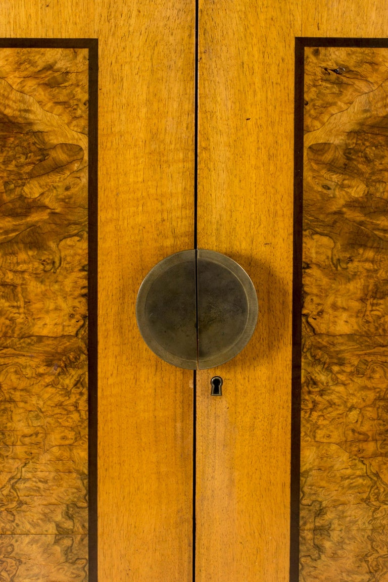 Stately functionalist cabinet by Erik Chambert, made from birch with birch root inlays. Large round brass door handle that splits seamlessly when the cabinet is opened. Elegant inside made from darker wood with contrasting drawer handles. A mirror