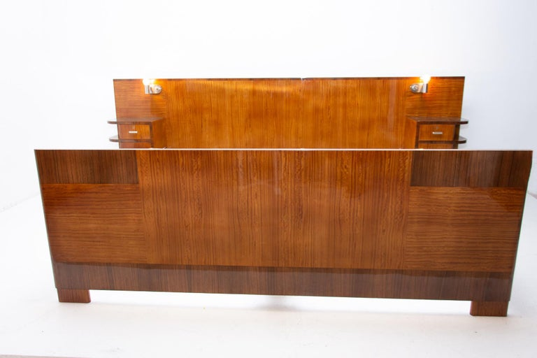 Double bed from the Bauhaus period, outstanding timeless design. It was made in the 1930s and designed by the Czechoslovak architect Vlastimil Brozek. Built-in bedside tables and lamps. Walnut veneer. Solid wood. The dimensions of the loading area