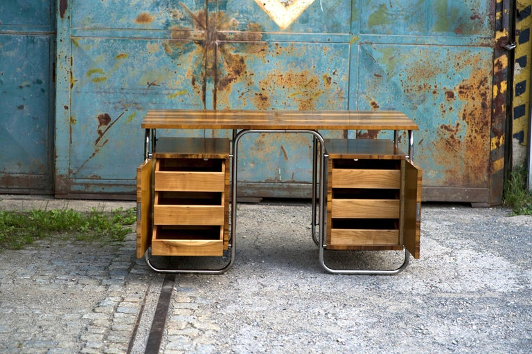 This functionalist desk was designed and manufactured in the Czech Republic in the 1930s. The walnut veneer with a very beautiful grain has been repainted, the chrome-plated steel tube construction cleaned and polished. Inside are 6 drawers with a