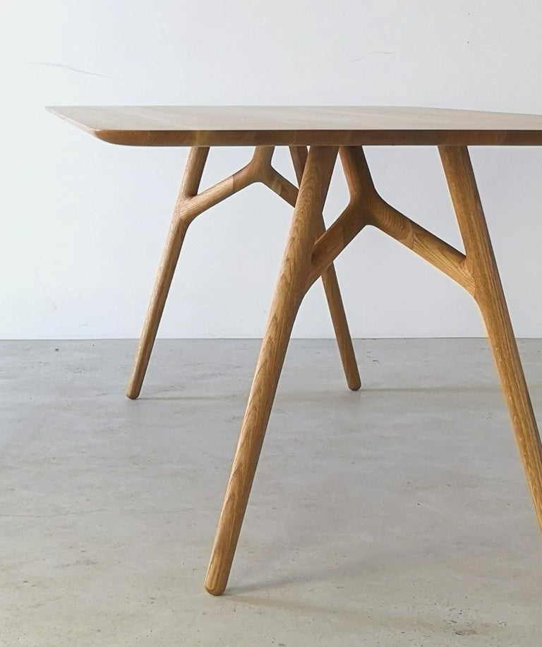 The Furcula by Izm Design is an elegantly handcrafted dining table featuring a sculpted