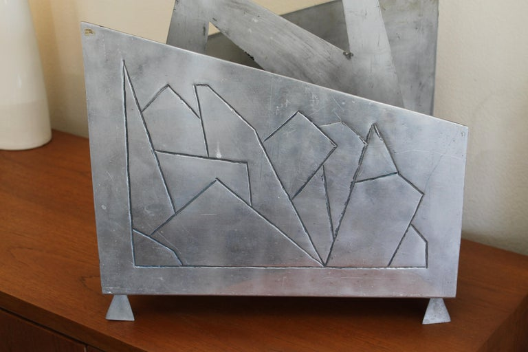 Studio one of a kind aluminum magazine rack. Could also function as a log holder. Looks like a mountainscape. Rack measures: 18.25