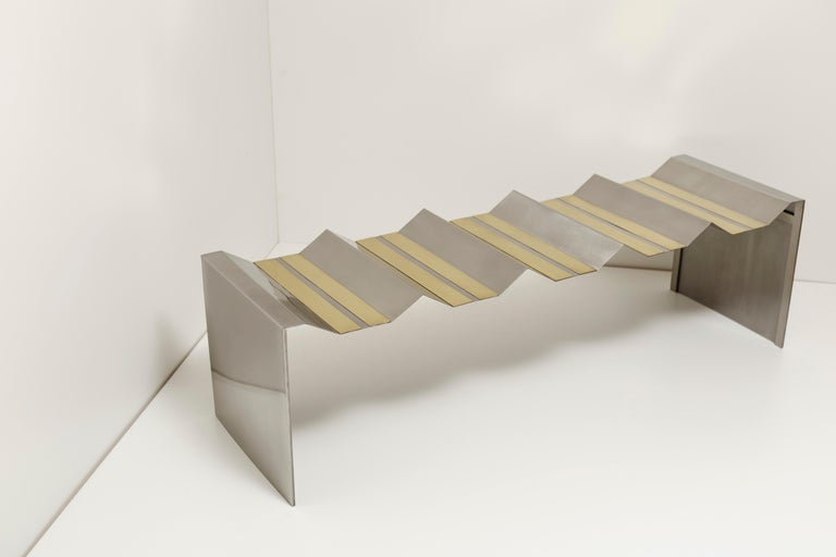 Futuristic bench by Ana Volante Studio The Moon Collection Dimensions: L 160 x W 50 x H 42 cm Materials: Stainless steel and brass  Ana Volante, founder of Ana Volante Studio, is a Venezuelan designer specialized in interior environments,