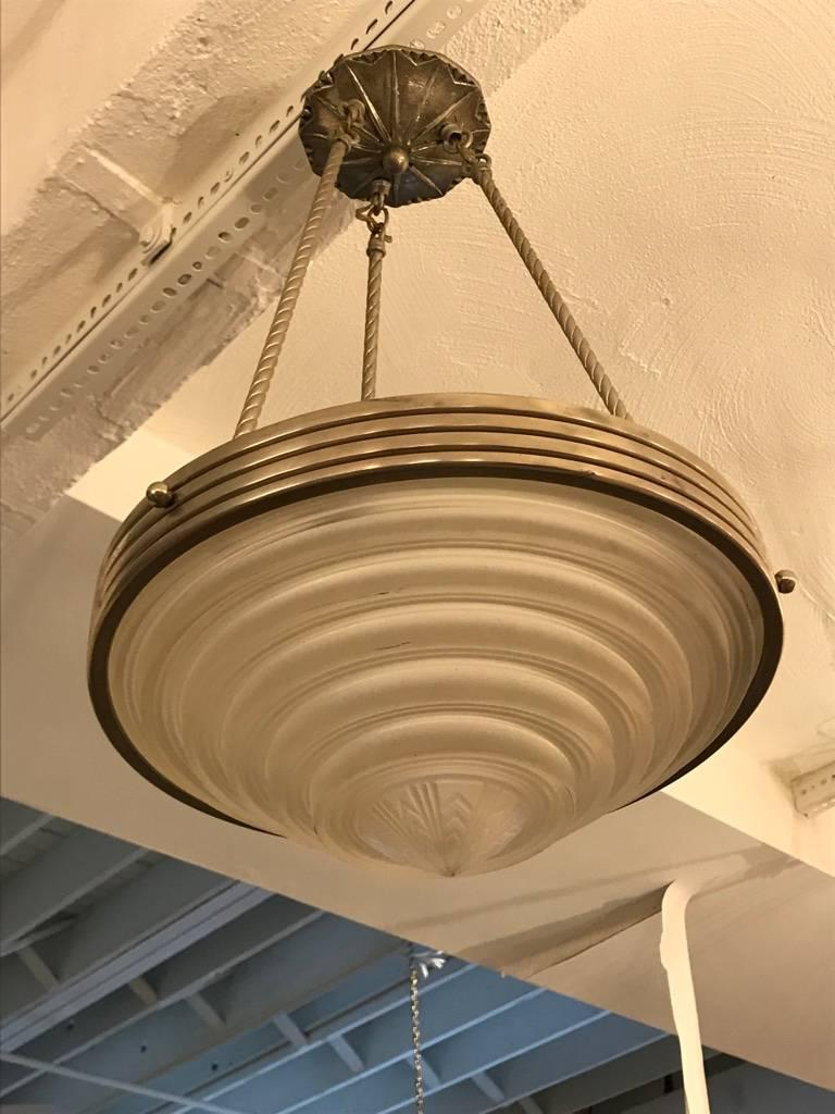 A stunning French Art Deco chandelier signed by Georges Leleu. With a beautiful center bowl in clear frosted glass with ribbed and geometric motif. Polished details on a nickel bronze frame. Having three rods and ceiling cap. Has been rewired for