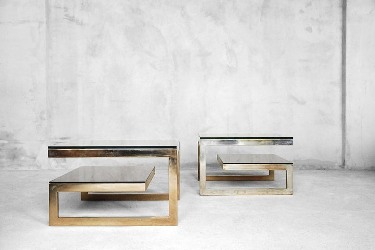 This set of two side tables was manufactured in Belgium by Dewulf Selection by Belgo-Chrom during the 1970s. This architectural two-tiered rectangular golden set in the Hollywood Regency style has a very eye-catching minimalistic design. On the