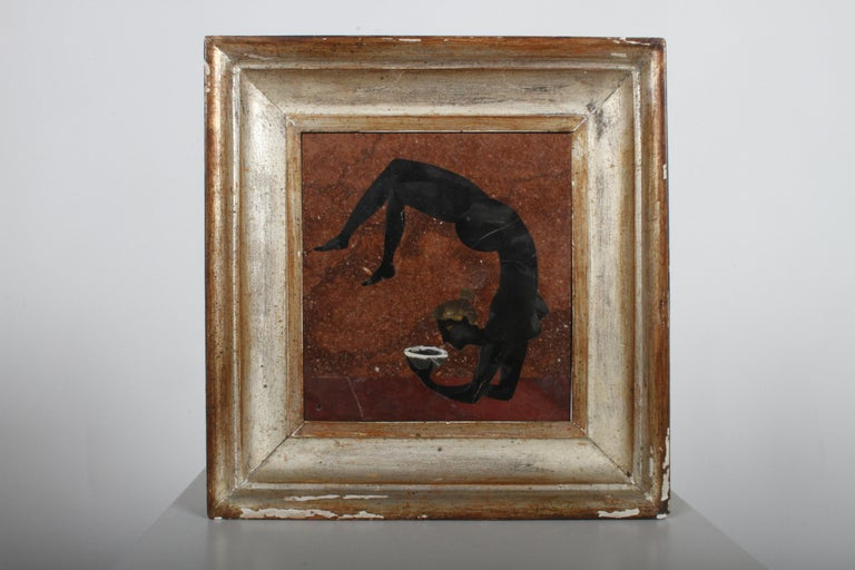 Giovanni Ugolini - Italy circa 1956, framed Pietra Dura polished stone mosaic plaque. Depicts a nude female acrobat, holding a bowl. Verso: retains original label, marked made in Italy 1956, plus artist name Calde. Light scuffs to plaque, wear to