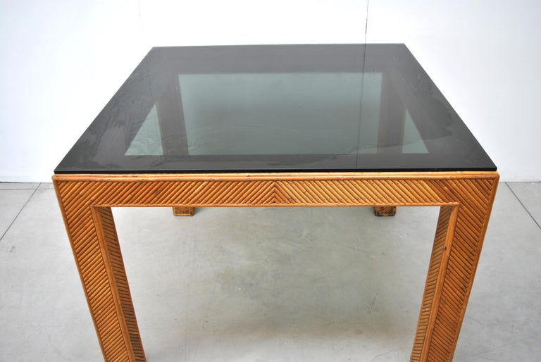 Italian rattan table, early 1970s with smoked glass top.
