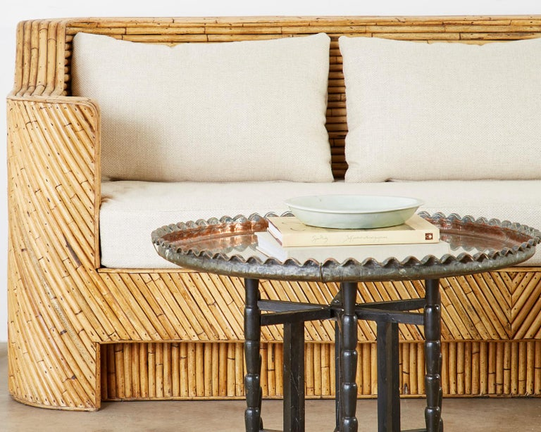 Stunning Hollywood Regency period bamboo rattan sofa made in the organic modern style. Constructed from split bamboo rattan this sofa represents everything wonderful about the modern use of bamboo. Incredible geometric patterns abound reminiscent of