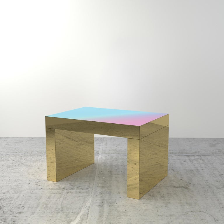 Gaby is a contemporary coffee table that presents shades of color integrated in the table top, which is paired with a chunky and highly reflective gold metallic base.   The multicolored shades mix to create new combinations of colors on the top from