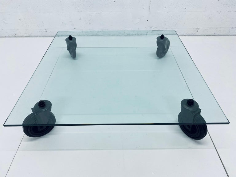 Designed by Gae Aulenti, this low coffee table consists of a tempered glass top supported by four black industrial wheels and was produced by Fontana Arte and imported by Luminaire.  An Industrial trolley used at the Fontana Arte plant to