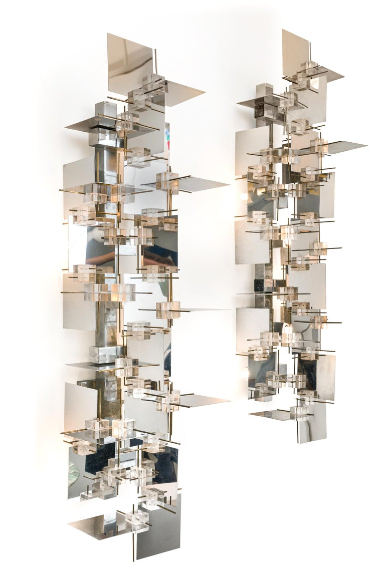 A rare and impressive pair of sconces by Gaetano Sciolari. The chrome panels create a wonderful effect reflecting the light at every angle. There is some discoloration to the Lucite cubes that is only apparent when observed closely.