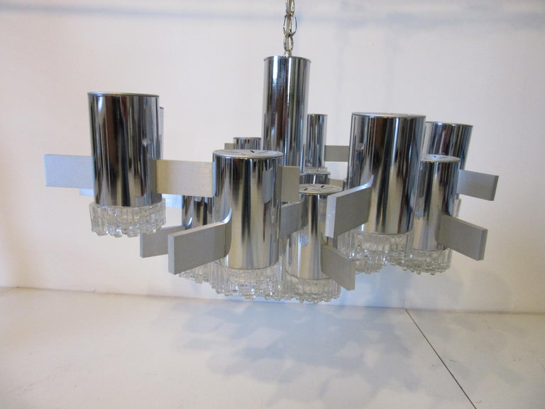 A chrome tubed hanging light fixture with 16 molded glass patterned lamp ends tied together by brushed aluminum bars . This impressive piece of sculptural lighting would enhance any entrance way, dining room or large area , can be hung at any height