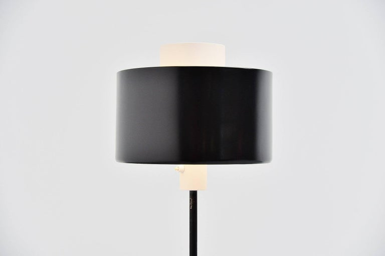 Nice modernist floor lamp designed by Gaetano Sciolari and manufactured by Stilnovo, Italy, 1954. This floor lamp has a weighted base, black painted. The shade has a white center part with a black diffuser shade around it. This lamp gives very nice