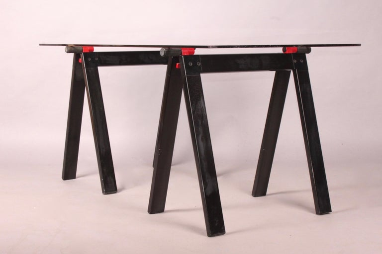 Gaetano working table by Gae Aulenti for Zanotta with original glass top, supported by two black and red enameled metal folding working horses alike base, one plastic base is missing.